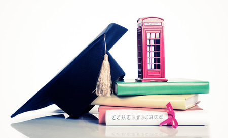 diploma: education in Great Britain Concept. Stack of books, mortarboard, diploma and red phone box - symbol of England