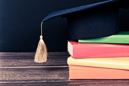 mortarboard: Graduation mortarboard on top of stack of books Stock Photo