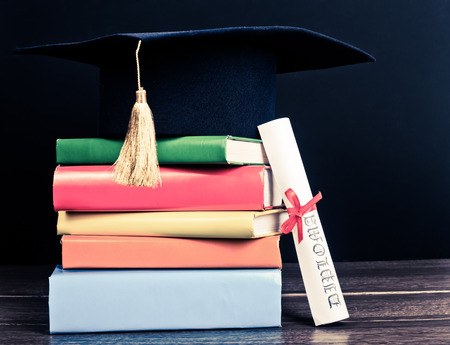 mortar hat: A mortarboard and graduation scroll, tied with red ribbon, on a stack of books Stock Photo