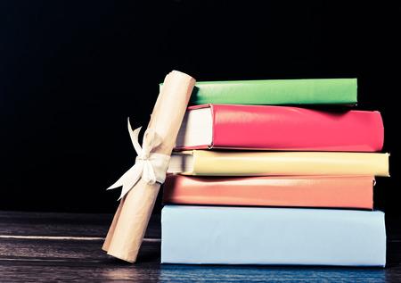 diploma: Pila de libros de texto y la graduación de la voluta