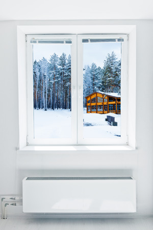 freshly fallen snow: Wooden house in a nature area covered with freshly fallen snow seen through the window Stock Photo