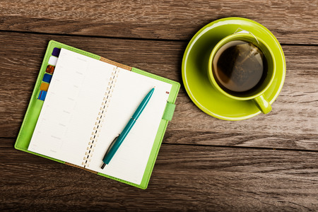 cup of tea, pen, opened organizer on the wooden table photo