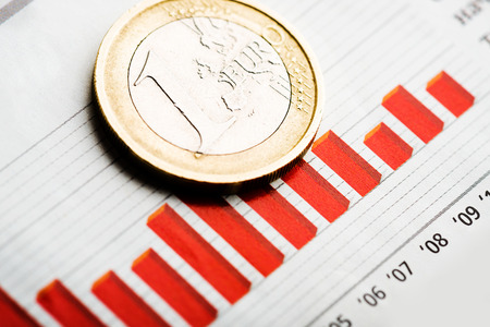 fluctuate: One euro coin on fluctuating graph. Rate of euro (shallow DOF) Stock Photo
