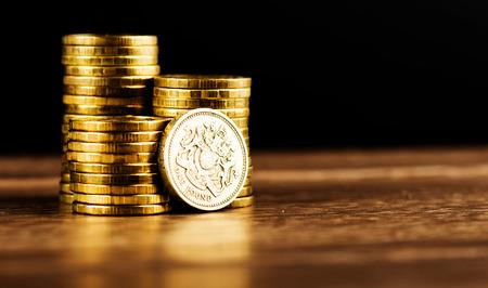 파운드 GBP 동전과 금 돈을 책상에 스톡 콘텐츠