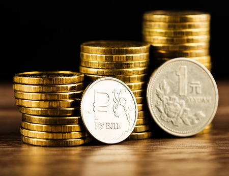 correlation: The Russian rouble coin and Chinese One Yuan Coin and gold money on the desk Stock Photo