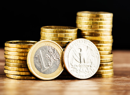 us coin: one euro coin and us quarter dollar coin and gold money on the desk