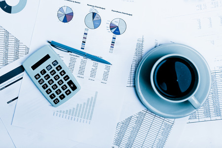blue  toned: Business report. Cup of coffee on document. Accounting.  Blue toned