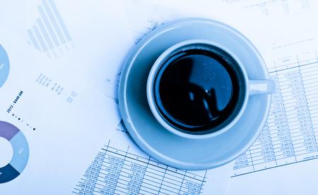 cuadro sinoptico: escritorio de la oficina en la mañana con una taza de café y documentos financieros. Azul tonificado