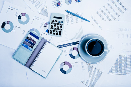 economist: Close of business workplace with financial reports and office stuff.  Blue toned Stock Photo