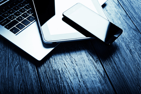 personal information: keyboard with phone and tablet pc on wooden desk.  Blue toned Stock Photo