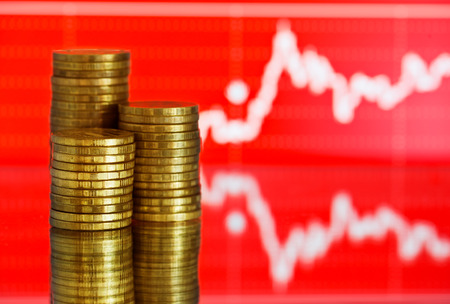 fluctuate: gold money. Fluctuating graph on red background. Stock Photo