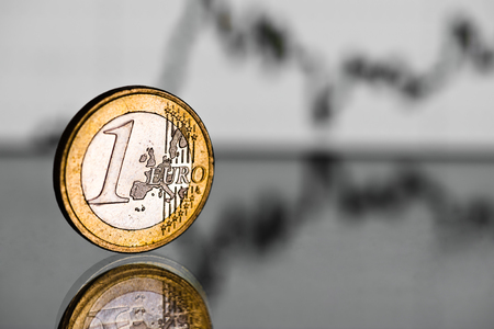 fluctuate: One euro coin. Fluctuating graph on  background. Rate of the euro  (shallow DOF)