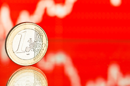 fluctuate: euro coin. Fluctuating graph on red background. Rate of the euro (shallow DOF)