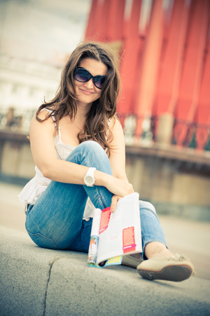 fashion magazine: Outdoor portrait of young woman with fashion magazine