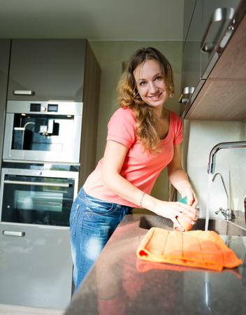 lavar platos: Feliz taza de lava de la mujer joven. Cocina. Lavavajillas.