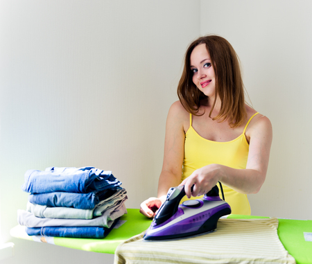 woman ironing: Happy young beautiful woman ironing clothes. Housework