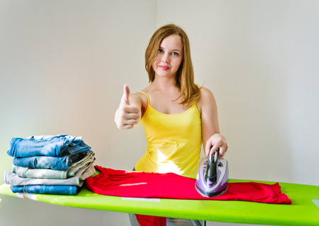 woman ironing: Young beautiful woman ironing clothes in room on grey background
