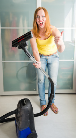 thumbup: Woman cleaning the house with the Vacuum Cleaner Stock Photo