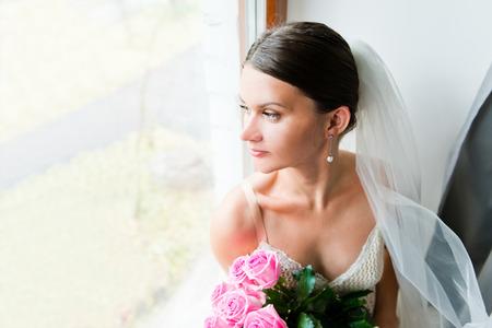 waits: Young beautiful bride waits for groom near the window Stock Photo