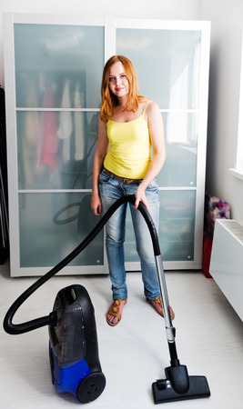 charwoman: Woman cleaning the house with the Vacuum Cleaner Stock Photo