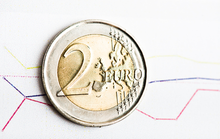 fluctuate: two euro coin on fluctuating graph. Rate of euro (shallow DOF) Stock Photo