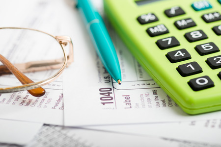taxes: Business work station with paperwork income tax return, calculator and pen Stock Photo