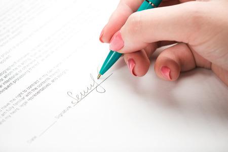 contrato de trabajo: mano femenina que firma un contrato.
