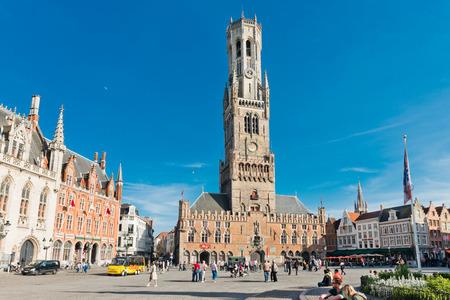 bruges: Bruges, Belgium - MAY 27, 2015: The Belfry Tower of Bruges. Tourists on Grote Markt square in Bruges, Belgium. Bruges is touristic center of Flanders city of Brugge, Belgium. Editorial