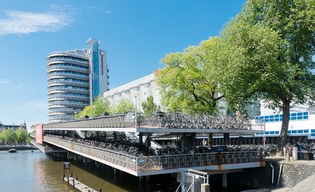 parking station: AMSTERDAM, NETHERLANDS - JUNE 01, 2015: Huge bicycle parking in front of the central station Amsterdam.  Amsterdam is the capital city and most populous city of the Kingdom of the Netherlands.