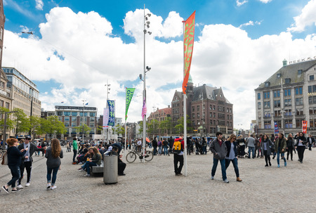 AMSTERDAM, NETHERLANDS - JUNE 01, 2015:  Tourists at the Dam Square. It is one of three palaces in the Netherlands which is at the disposal of Queen Beatrix by Act of Parliament