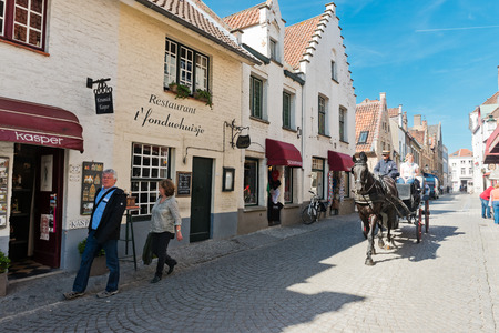 belgian horse: Bruges, Belgium - MAY 27, 2015: Horse carriage and tourists on the streets of Brugge. Belgian city of Bruges (Brugge) is UNESCO world heritage listed for its medieval center.