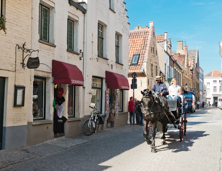 belgian horse: Bruges, Belgium - MAY 27, 2015: Horse carriage and tourists on the streets of Brugge. Belgian city of Bruges (Brugge)