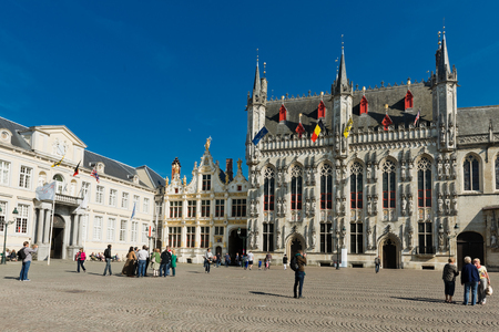 bruges: Bruges, Belgium - MAY 27, 2015: Tourist on Burg square with City Hall in Bruges, Belgium Editorial