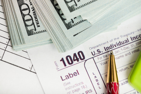 irs: federal income tax return IRS 1040 documents with pen, calculator, dollars
