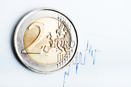 fluctuate: euro coin on fluctuating graph. Rate of euro (shallow DOF)