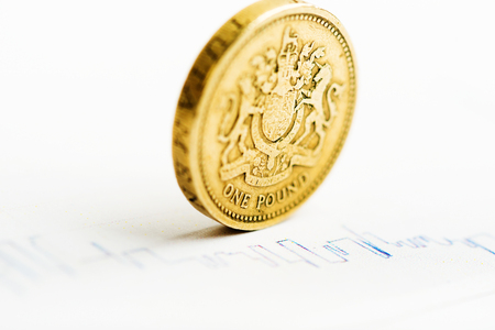 devaluation: One pound coin on fluctuating graph. Rate of the pound sterling (shallow DOF)