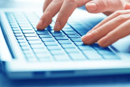 Primer plano de las manos femeninas escribiendo en el teclado