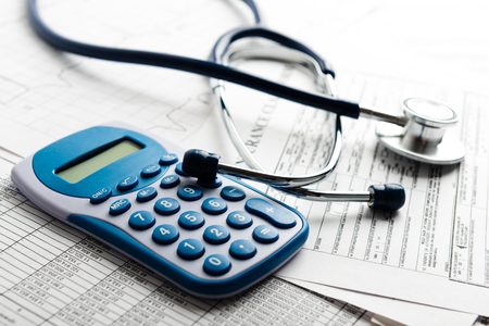 stethoscope: Health care costs. Stethoscope and calculator symbol for health care costs or medical insurance