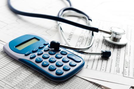 calculadora: Los costos de salud. Estetoscopio y calculadora símbolo de los costos de atención de salud o seguro médico