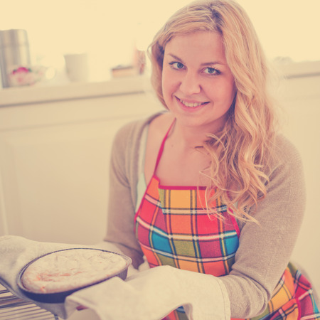 cross hatch: Woman pulling pie from oven . Stock Photo