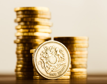 money pound: pound GBP coin and gold money on the desk
