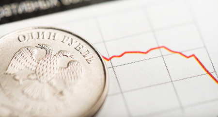 fluctuate: rouble goes down in value. One rouble coin on fluctuating graph. Rate of the Russian rouble (shallow DOF)