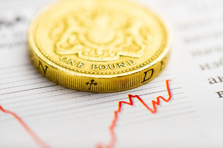 trading stocks: One pound coin on fluctuating graph. Rate of the pound sterling (shallow DOF)
