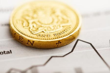 sterlina: Una moneta da una sterlina sul grafico fluttuante. Tasso della sterlina (shallow DOF)