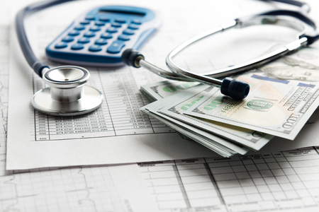 Stethoscope and calculator, symbol for health care costs or medical insurance