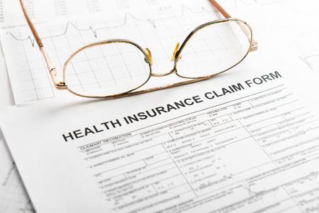 reimbursement: Health insurance claim form with glasses Stock Photo