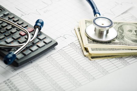 poor health: Stethoscope and calculator symbol for health care costs or medical insurance Stock Photo