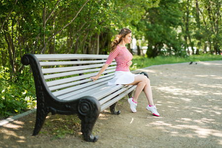 young brunette fashion model sits on a park bench photo