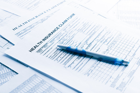 health insurance form, paperwork and questionnaire for insurance concepts. Blue toned Stock Photo