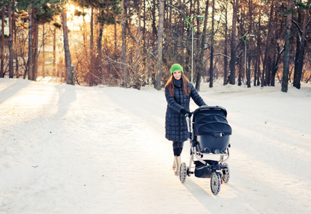 woman with stroller going for a walk in a park during lovely winter afternoon photo